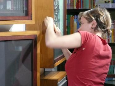 Anna Forlati alla libreria Giannino Stoppani mentre allestisce la mostra delle tavole de I libri di Maliq